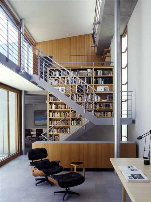 Woollahra house: the void space over a study/dining area with limestone floor tiles, off-form concrete, blackbutt veneer joinery and an eames lounge chair, Artek stool and Tizio lamp