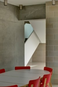 Block House house: Artek dining table and chairs in bright red contrast well with the grey and white background.
